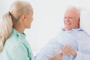 Elderly man in nursing home with caregiver